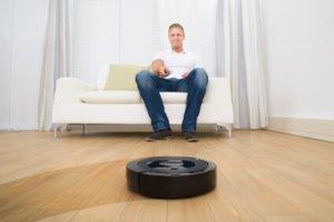 Chico manejando una aspiradora robótica desde el sofá