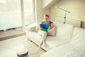 Mujer contenta de su robot aspirador bueno y barato